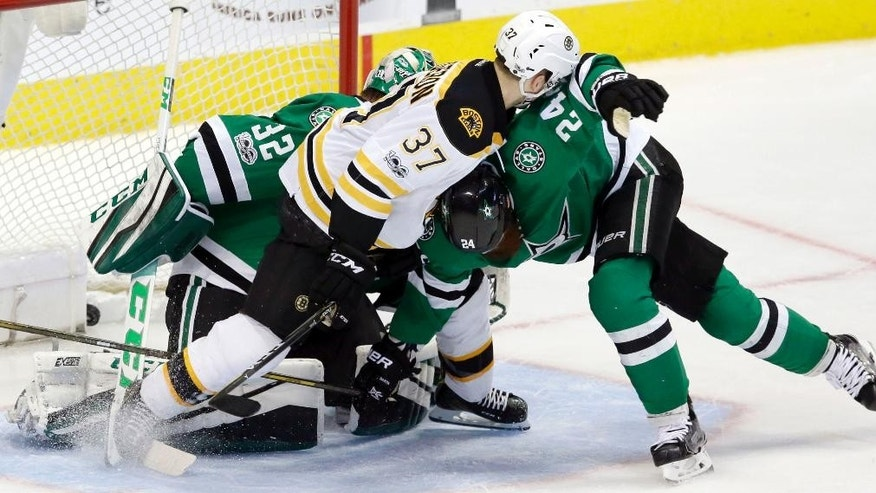 Boston Bruins center Patrice Bergeron (37) gets the puck into the net to score a goal against Dallas Stars defenseman Jordie Benn (24) and goalie Kari Lehtonen (32) during the second period of an NHL hockey game in Dallas, Sunday, Feb. 26, 2017. (AP Photo/LM Otero)