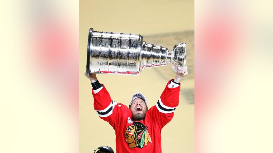 FILE - In this June 10, 2015, file photo, Chicago Blackhawks' Kimmo Timonen, of Finland, hoists the Stanley Cup trophy after defeating the Tampa Bay Lightning in Game 6 of the NHL hockey Stanley Cup Final series in Chicago. When the Chicago Blackhawks won it all in 2015, they didn't mind sending an extra second-round pick to the Flyers for Kimmo Timonen for reaching the Cup Final and the defenseman playing in at least half their games.  (AP Photo/Charles Rex Arbogast, File)