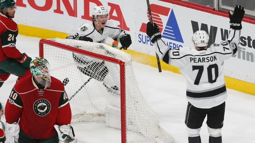 Minnesota Wild goalie Devan Dubnyk, left, gives up a goal to the celebrating Los Angeles Kings' Tanner Pearson, right, in the first period of an NHL hockey game, Monday, Feb. 27, 2017, in St. Paul, Minn. (AP Photo/Jim Mone)