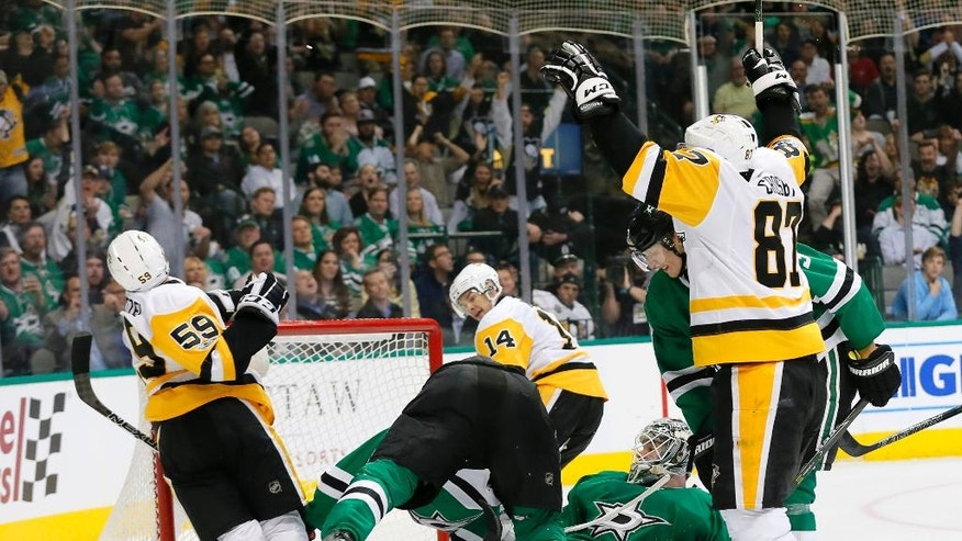 Pittsburgh Penguins' Sidney Crosby (87) celebrates after Jake Guentzel (59) scored against Dallas Stars' Kari Lehtonen, center, laying on ice, of Finland, in the second period of an NHL hockey game, Tuesday, Feb. 28, 2017, in Dallas. (AP Photo/Tony Gutierrez)
