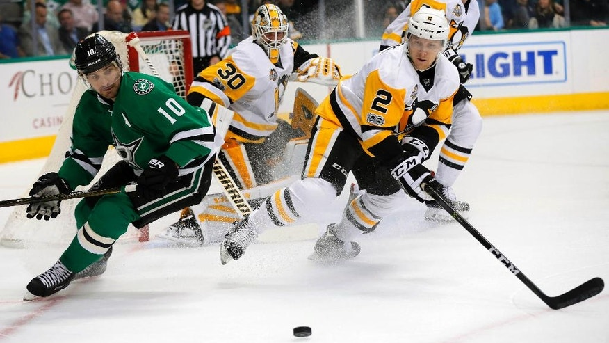 Dallas Stars left wing Patrick Sharp (10) and Pittsburgh Penguins defenseman Chad Ruhwedel (2) chase after a loose puck in the first period of an NHL hockey game as Penguins goalie Matt Murray (30) watches on Tuesday, Feb. 28, 2017, in Dallas. (AP Photo/Tony Gutierrez)