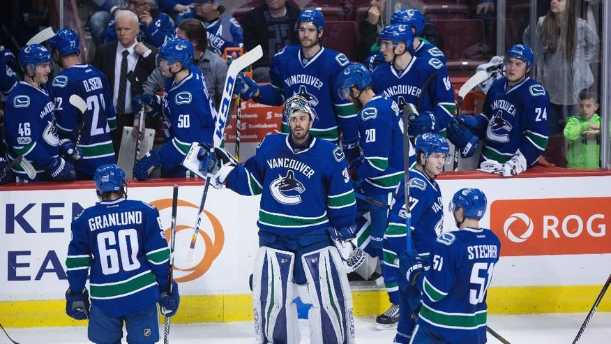 Vancouver Canucks goalie Ryan Miller, center, and teammates leave the ice after a loss to the Detroit Red Wings during overtime in an NHL hockey game Tuesday, Feb. 28, 2017, in Vancouver, British Columbia. (Darryl Dyck/The Canadian Press via AP)