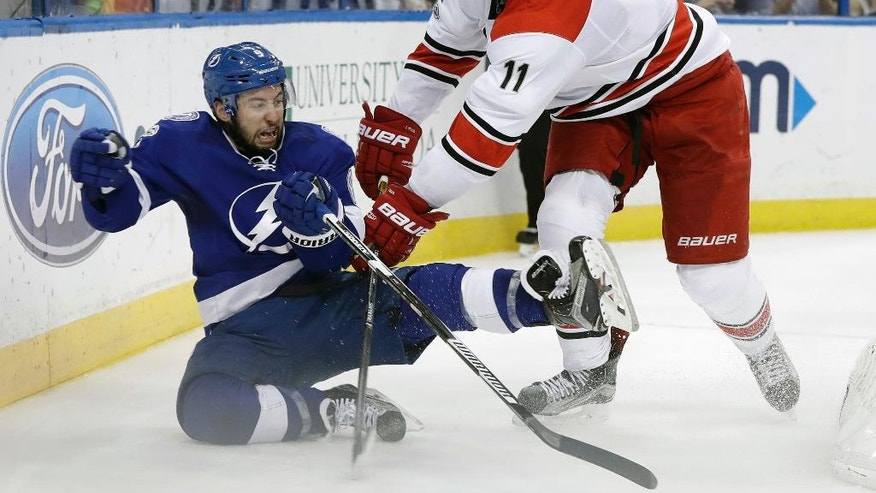Carolina Hurricanes center Jordan Staal (11) knocks down Tampa Bay Lightning center Tyler Johnson (9) during the second period of an NHL hockey game Wednesday, March 1, 2017, in Tampa, Fla. (AP Photo/Chris O'Meara)