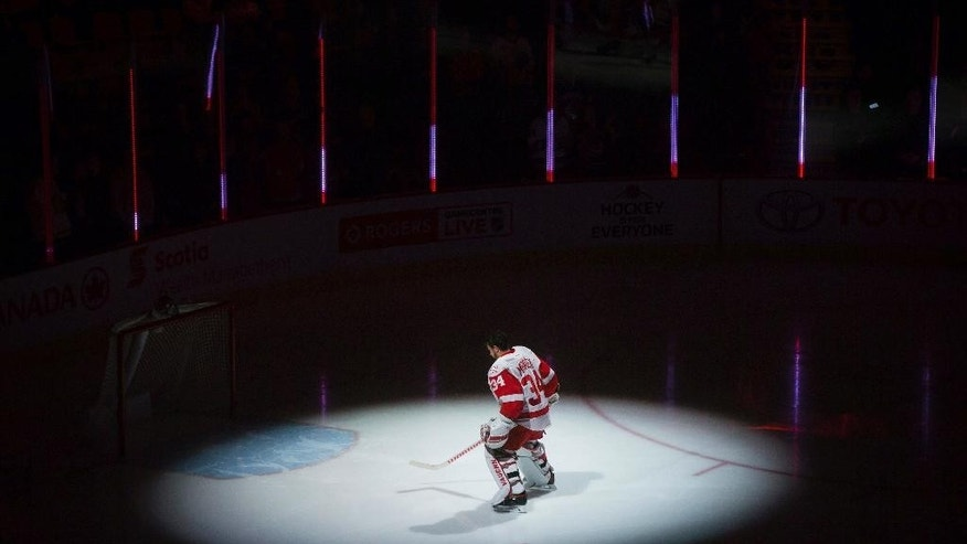 Detroit Red Wings' goalie Petr Mrazek, of the Czech Republic, is illuminated by a spotlight as he skates to his net after the singing of the national anthems before the team's NHL hockey game against the Vancouver Canucks on Tuesday, Feb. 28, 2017, in Vancouver, British Columbia. (Darryl Dyck/The Canadian Press via AP)