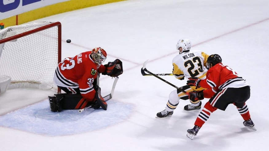 Pittsburgh Penguins' Scott Wilson (23) scores past Chicago Blackhawks goalie Scott Darling, left, as Michal Kempny also defends during the second period of an NHL hockey game Wednesday, March 1, 2017, in Chicago. The goal was awarded after video review. (AP Photo/Charles Rex Arbogast)