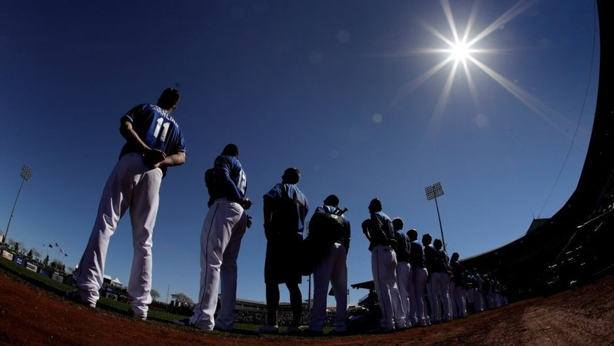 In this image taken with a fisheye lens, members of the Kansas City Royals stand for the national anthem before a spring training baseball game against the Chicago Cubs Wednesday, March 1, 2017, in Surprise, Ariz. (AP Photo/Charlie Riedel)