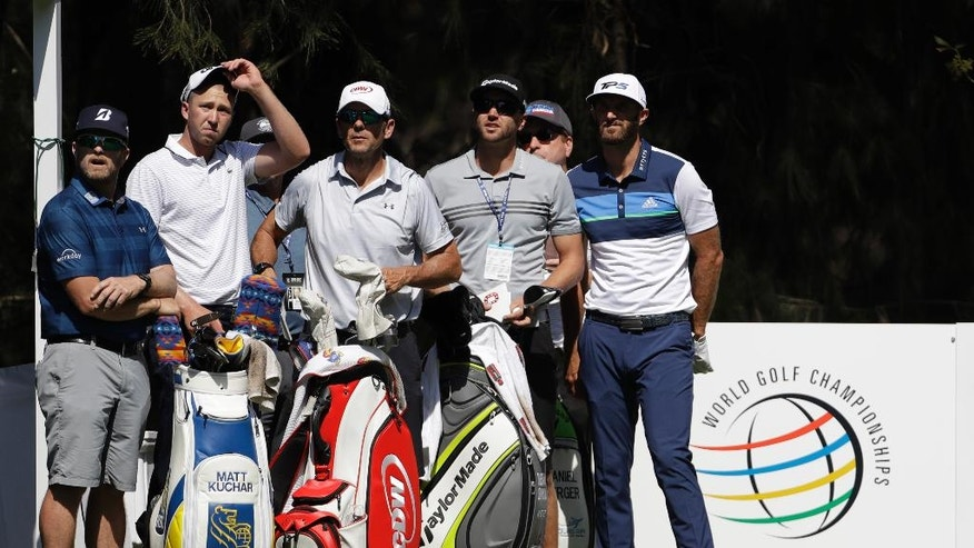 U.S. golfers Dustin Johnson, right, and Daniel Berger, second left, stand with caddies as they watch a drive by Gary Woodland, of the U.S., while practicing on the 9th hole at Chapultepec Golf Club a day before the start of the Mexico Championship in Mexico City, Wednesday, March 1, 2017. All but one of the world's top 50 golfers will contest the World Golf Championship PGA event, which this year relocated to Mexico City from the Trump National Doral Resort in Florida. (AP Photo/Rebecca Blackwell)
