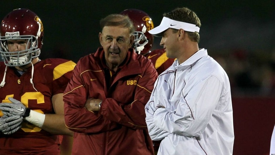 LOS ANGELES, CA - SEPTEMBER 11: Head coach Lane Kiffin (R) and his father and defensive coordinator Monte Kiffin of the USC Trojans talk during warmups for their game with the Virginia Cavaliers at Los Angeles Memorial Coliseum on September 11, 2010 in Los Angeles, California. (Photo by Stephen Dunn/Getty Images)