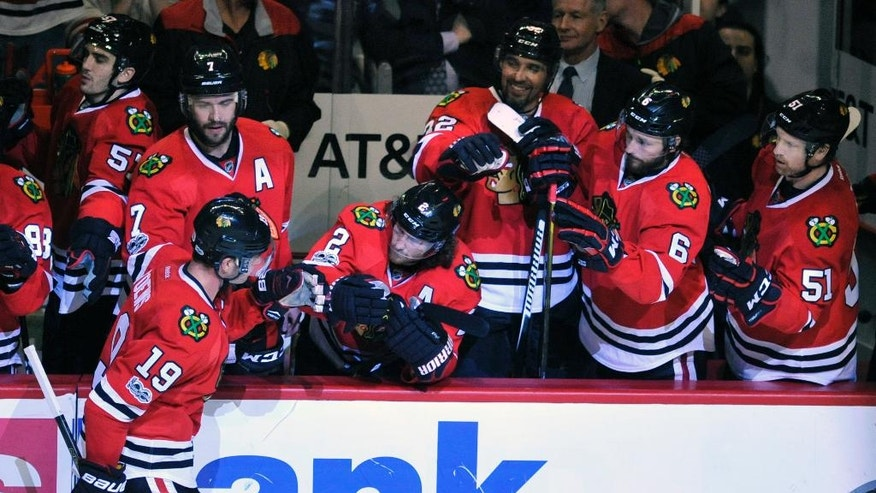 Chicago Blackhawks' Jonathan Toews (19) celebrates with teammates on the bench after scoring a goal during a shootout in an NHL hockey game against the New York Islanders, Friday, March 3, 2017, in Chicago. (AP Photo/Paul Beaty)
