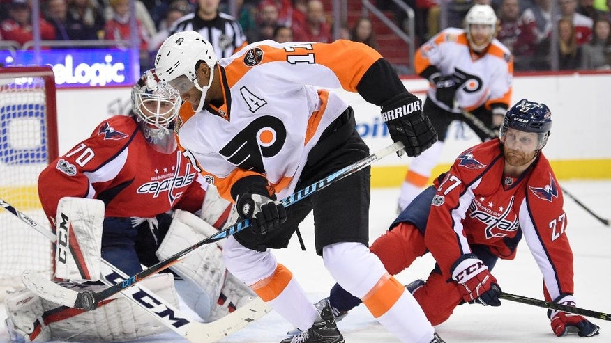 Philadelphia Flyers right wing Wayne Simmonds (17) controls the puck in front of Washington Capitals goalie Braden Holtby (70) and defenseman Karl Alzner (27) during the second period of an NHL hockey game, Saturday, March 4, 2017, in Washington. (AP Photo/Nick Wass)
