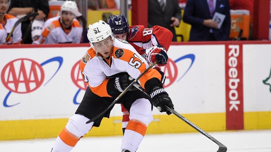 Philadelphia Flyers center Valtteri Filppula (51), of Finland, reaches for the puck against Washington Capitals center Jay Beagle (83) during the second period of an NHL hockey game, Saturday, March 4, 2017, in Washington. (AP Photo/Nick Wass)