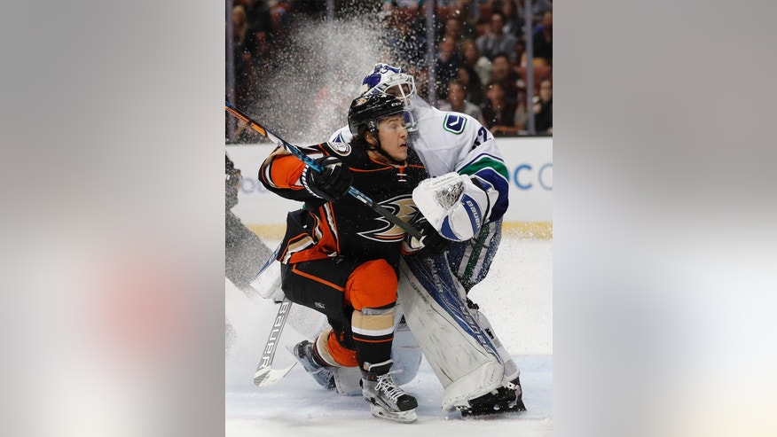 Anaheim Ducks' Brandon Montour, left, runs into Vancouver Canucks goalie Richard Bachman during the second period of an NHL hockey game, Sunday, March 5, 2017, in Anaheim, Calif. (AP Photo/Jae C. Hong)