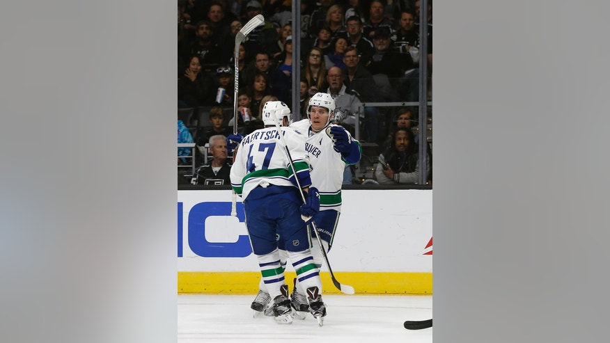 Vancouver Canucks center Bo Horvat, right, congratulates left wing Sven Baertschi, left, of Switzerland, for scoring against the Los Angeles Kings during the first period of an NHL hockey game in Los Angeles, Saturday, March 4, 2017. (AP Photo/Alex Gallardo)