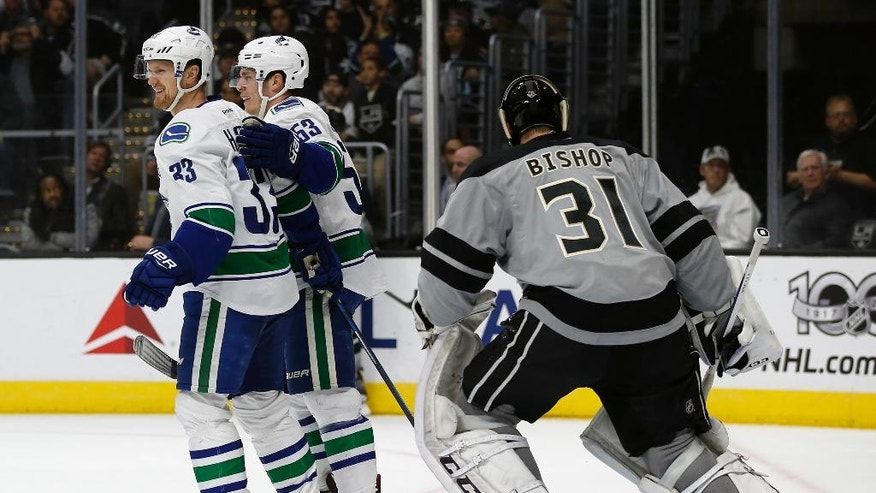 Los Angeles Kings goalie Ben Bishop (31) looks away as Vancouver Canucks center Henrik Sedin (33), of Sweden, and center Bo Horvat (53) celebrate Sedin's goal during the first period of an NHL hockey game in Los Angeles, Saturday, March 4, 2017. (AP Photo/Alex Gallardo)