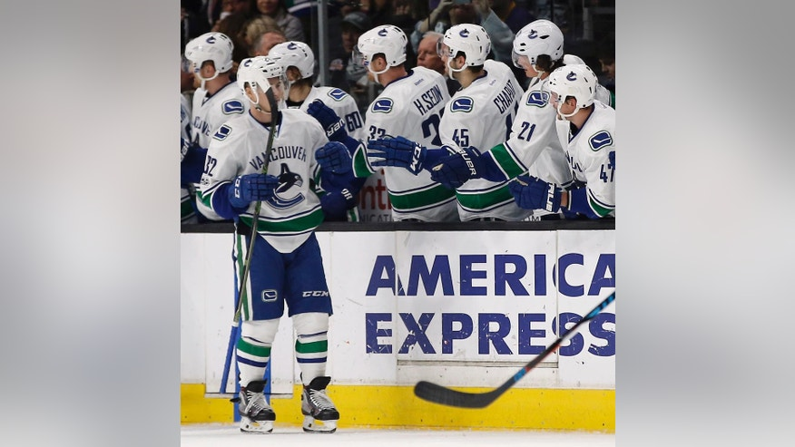 Vancouver Canucks left wing Nikolay Goldobin, left, of Russia, gets congratulations from his teammates on the bench after scoring against the Los Angeles Kings during the second period of an NHL hockey game in Los Angeles, Saturday, March 4, 2017. (AP Photo/Alex Gallardo)