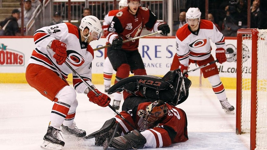 Arizona Coyotes goalie Mike Smith, center, makes a diving save on the shot by Carolina Hurricanes' Phillip Di Giuseppe (34) during the first period of an NHL hockey game, Sunday, March 5, 2017, in Glendale, Ariz. (AP Photo/Ralph Freso)
