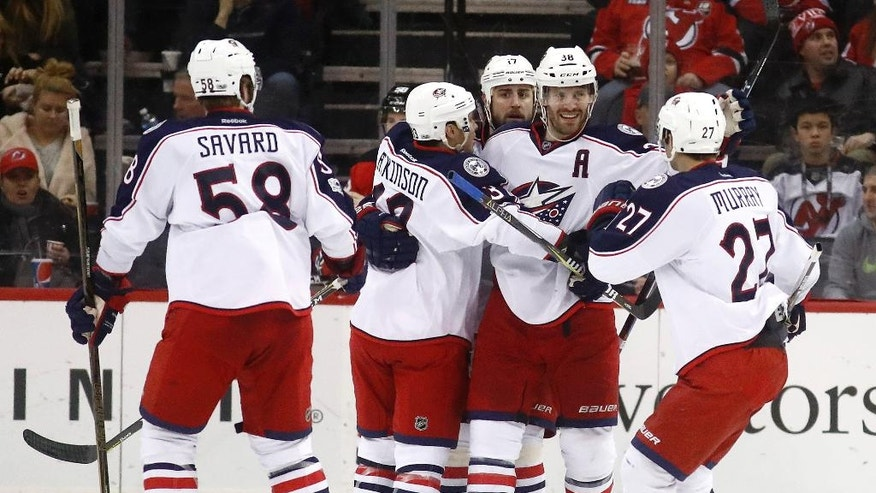 Columbus Blue Jackets center Boone Jenner, second from right, is congratulated after scoring a goal on the New Jersey Devils during the second period of an NHL hockey game, Sunday, March 5, 2017, in Newark, N.J. (AP Photo/Julio Cortez)