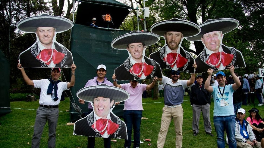 Mexican golf fans hold mariachi motif cutouts depicting from left to right; Jordan Spieth, of the U.S.; Bubba Watson, of the U.S.; Northern Ireland's Rory McIlroy; Dustin Johnson and Phil Mickelson both of the U.S., during round three of the Mexico Championship at Chapultepec Golf Club in Mexico City, Saturday, March 4, 2017. All but one of the world's top 50 golfers are contesting the World Golf Championship PGA event, which this year relocated to Mexico City from the Trump National Doral Resort in Florida. (AP Photo/Eduardo Verdugo)
