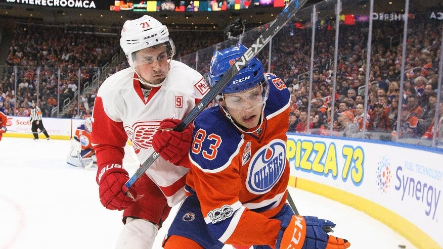 Detroit Red Wings' Dylan Larkin (71) and Edmonton Oilers' Matthew Benning (83) compete for the puck during the second period of an NHL hockey game Saturday, March 4, 2017, in Edmonton, Alberta. (Jason Franson/The Canadian Press via AP)