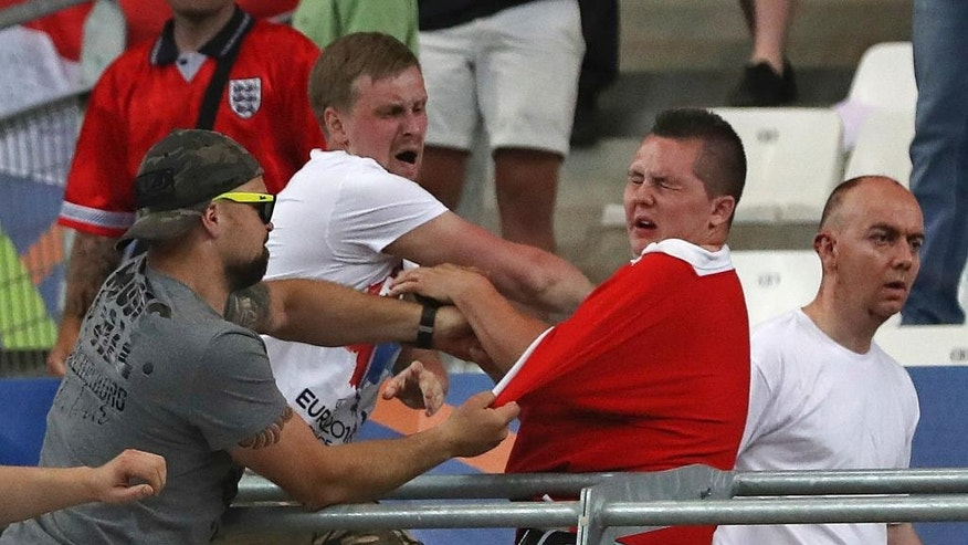 FILE - In this Saturday, June 11, 2016 file photo Russian supporters attack an England fan at the end of the Euro 2016 Group B soccer match between England and Russia, at the Velodrome stadium in Marseille, France. A Russian lawmaker has proposed an unorthodox solution to the country's football hooliganism woes ahead of next year's World Cup, legalize it and turn it into a spectator sport. (AP Photo/Thanassis Stavrakis, File)