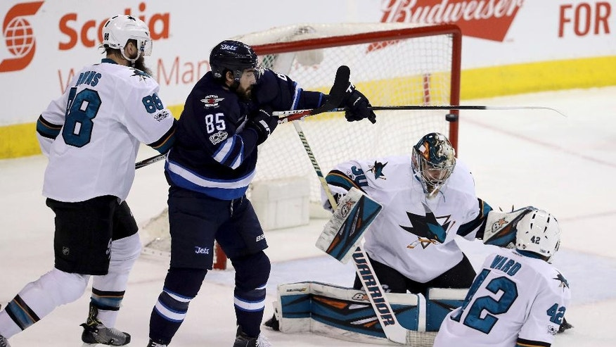 Winnipeg Jets' Mathieu Perreault (85) tries to deflect a shot by Josh Morrissey (44), not seen, who beats San Jose Sharks goaltender Aaron Dell (30) to score during first period NHL hockey action in Winnipeg, Monday, March 6, 2017. (Trevor Hagan/The Canadian Press via AP)