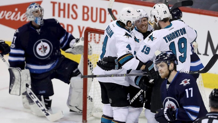 San Jose Sharks' Brenden Dillon (4), Joe Pavelski (8) and Joe Thornton (19) celebrate after Pavelski scored on Winnipeg Jets goaltender Connor Hellebuyck (37) during first period NHL hockey action in Winnipeg, Monday, March 6, 2017. (Trevor Hagan/The Canadian Press via AP)