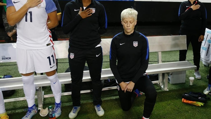 "FILE - In this Sunday, Sept. 18, 2016 file photo, United States' Megan Rapinoe, right, kneels next to teammates Ali Krieger (11) and Crystal Dunn (16) as the U.S. national anthem is played before an exhibition soccer match against Netherlands in Atlanta. Megan Rapinoe says she will respect a new U.S. Soccer Federation policy that says national team players ""shall stand respectfully"" during national anthems. The policy was approved last month but came to light Saturday, March 4, 2017 before the U.S. women's national team lost to England in a SheBelieves Cup match. (AP Photo/John Bazemore, File)"