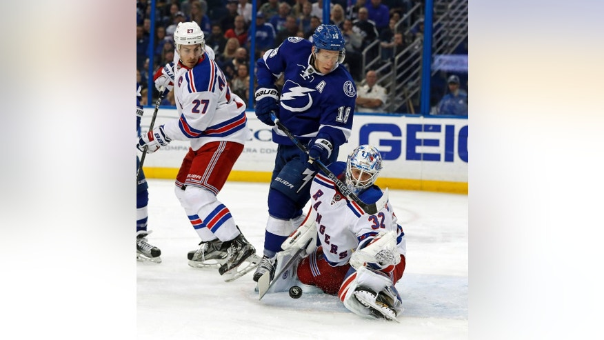 New York Rangers goalie Antti Raanta, of Finland, makes a save against Tampa Bay Lightning's Ondrej Palat, of the Czech Republic as Ryan McDonagh looks on during the second period of an NHL hockey game, Monday, March 6, 2017, in Tampa, Fla. (AP Photo/Mike Carlson)