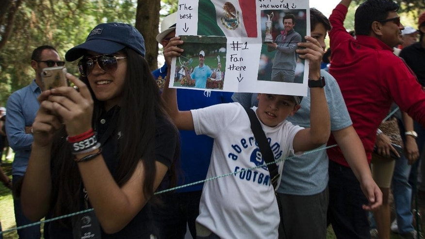 A fan of Northern Ireland golfer Rory McIlroy holds up pictures of him during the Mexico Championship at Chapultepec Golf Club in Mexico City, Sunday, March 5, 2017. All but one of the world's top 50 golfers are contesting the World Golf Championship PGA event, which this year relocated to Mexico City from the Trump National Doral Resort in Florida. (AP Photo/Christian Palma)