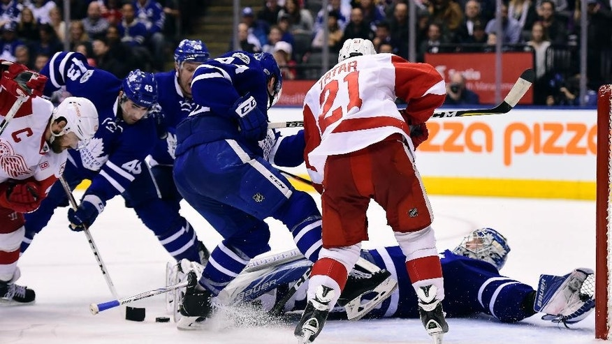 Toronto Maple Leafs goalie Frederik Andersen (31) lies prone on the ice as teammates Morgan Rielly (44) and Nazem Kadri (43) defend against Detroit Red Wings' Tomas Tatar (21) and Henrik Zetterberg (40) attack during third period NHL hockey action in Toronto on Tuesday, March 7, 2017. (Frank Gunn/The Canadian Press via AP)