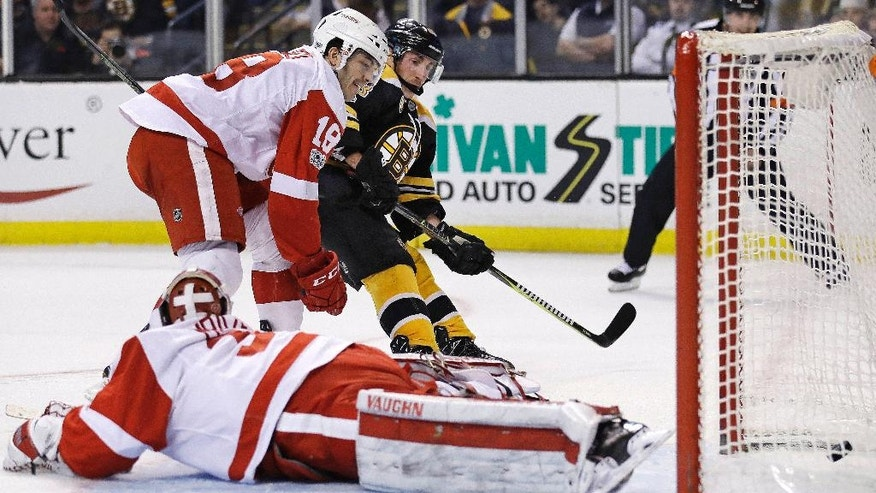 Boston Bruins left wing Brad Marchand, center, finds an opening for a goal behind Detroit Red Wings goalie Petr Mrazek (34) during the second period of an NHL hockey game in Boston, Wednesday, March 8, 2017. At left is defenseman Robbie Russo (18). (AP Photo/Charles Krupa)