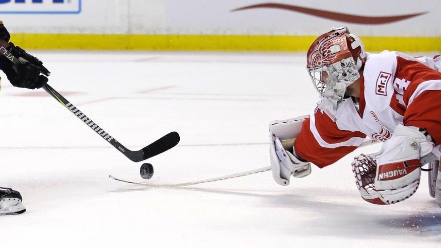 Detroit Red Wings goalie Petr Mrazek, right, tries unsuccessfully to knock the puck off the stick of Boston Bruins left wing Brad Marchand on a goal during the second period of an NHL hockey game in Boston, Wednesday, March 8, 2017. (AP Photo/Charles Krupa)