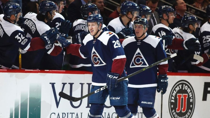Colorado Avalanche center Nathan MacKinnon, front, left, is congratulated after scoring a goal as he passes the team box with defenseman Tyson Barrie in the second period of an NHL hockey game against the New Jersey Devils, Thursday, March 9, 2017, in Denver. (AP Photo/David Zalubowski)
