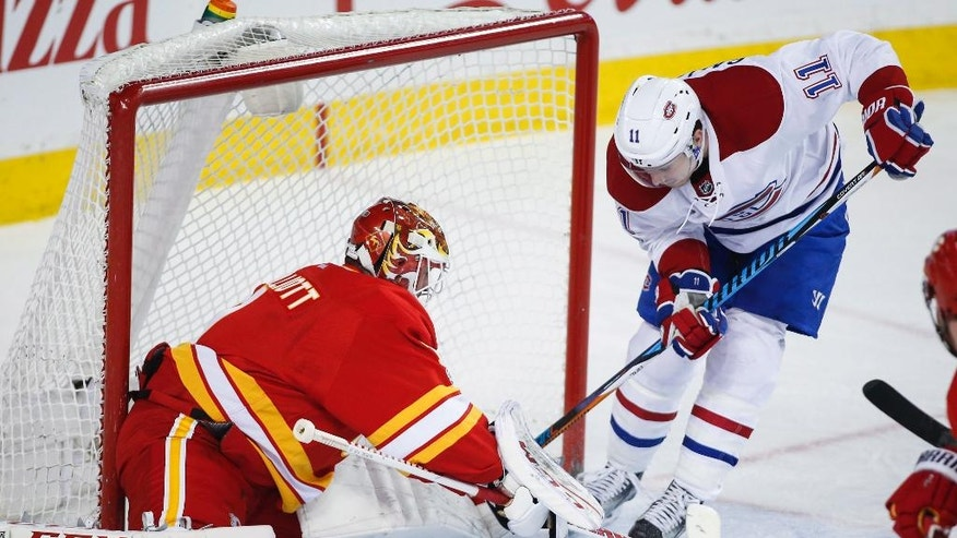 Montreal Canadiens' Brendan Gallagher, right, tries to get the puck past Calgary Flames goalie Brian Elliott during second-period NHL hockey game action in Calgary, Alberta, Thursday, March 9, 2017. (Jeff McIntosh/The Canadian Press via AP)