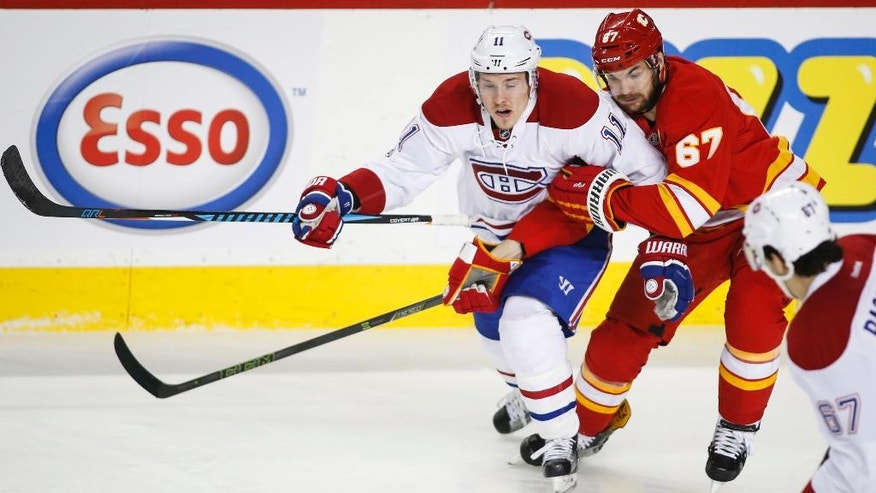 Montreal Canadiens' Brendan Gallagher, left, tries to get past Calgary Flames' Michael Frolik, of the Czech Republic, during second-period NHL hockey game action in Calgary, Alberta, Thursday, March 9, 2017. (Jeff McIntosh/The Canadian Press via AP)