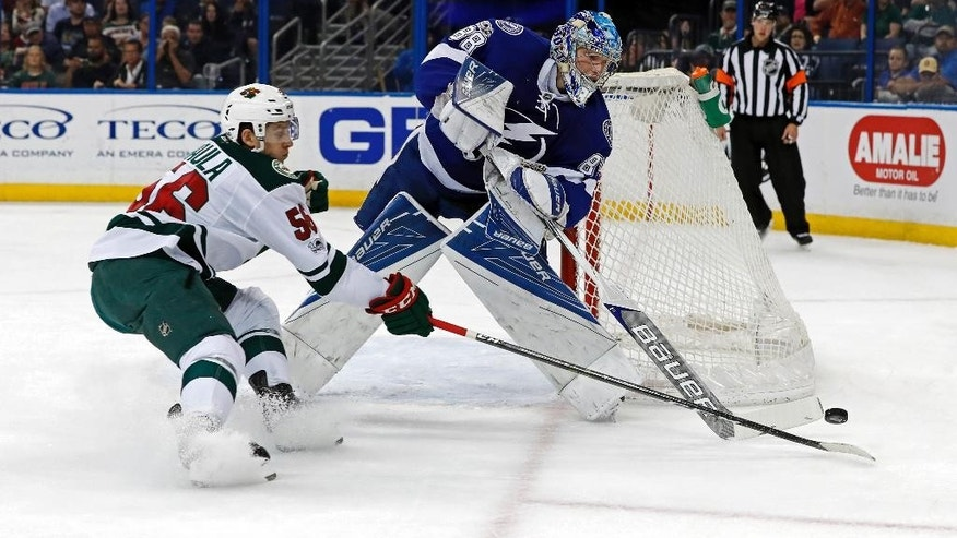 Tampa Bay Lightning goalie Andrei Vasilevskiy, of Russia, knocks the puck away from Minnesota Wild's Erik Haula, of Finland, during the first period of an NHL hockey game Thursday, March 9, 2017, in Tampa, Fla. (AP Photo/Mike Carlson)