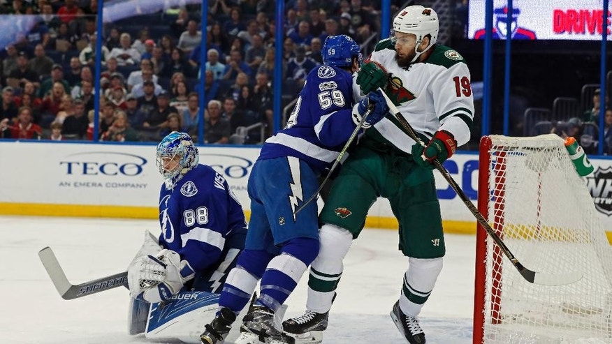 Tampa Bay Lightning's Jake Dotchin (59) clears Minnesota Wild's Martin Hanzal, of the Czech Republic, away from a rebound in front of goalie Andrei Vasilevskiy, of Russia, during the first period of an NHL hockey game Thursday, March 9, 2017, in Tampa, Fla. (AP Photo/Mike Carlson)