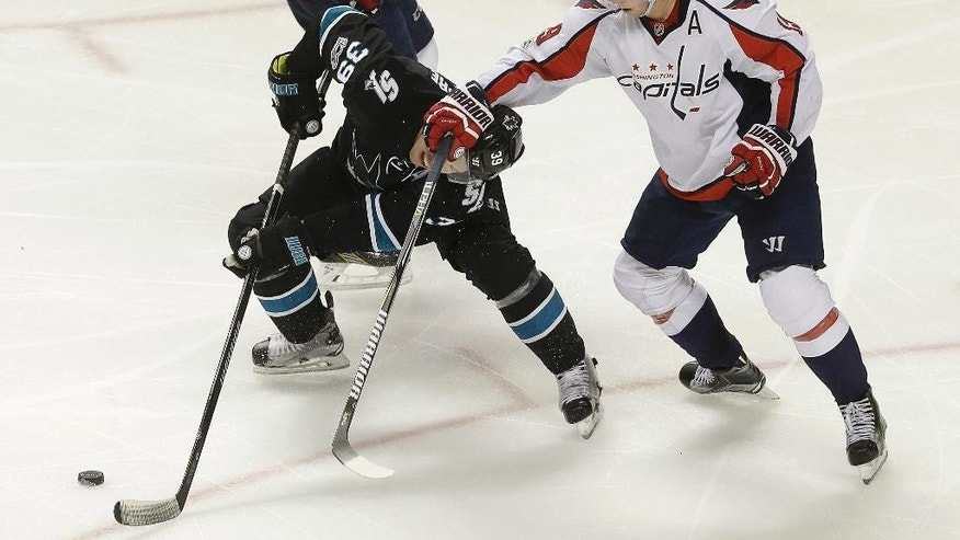 Washington Capitals center Nicklas Backstrom, right, from Sweden, grabs San Jose Sharks center Logan Couture (39) during the third period of an NHL hockey game in San Jose, Calif., Thursday, March 9, 2017. The Sharks won 4-2. (AP Photo/Jeff Chiu)