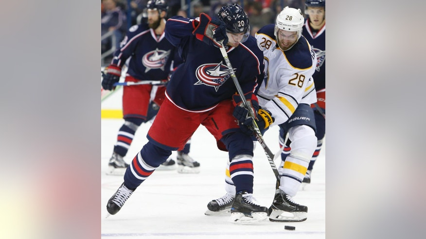 Columbus Blue Jackets' Brandon Saad, left, and Buffalo Sabres' Zemgus Girgensons, of Latvia, fight for the puck during the second period of an NHL hockey game Friday, March 10, 2017, in Columbus, Ohio. (AP Photo/Jay LaPrete)
