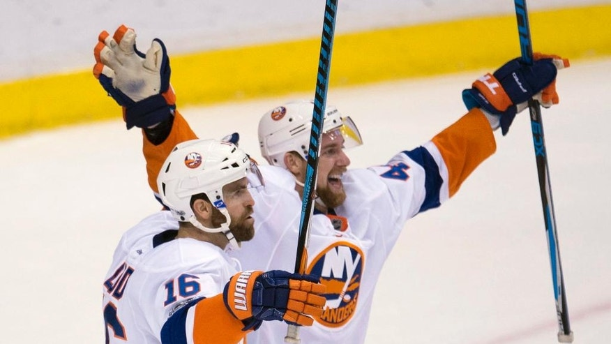 New York Islanders left wing Andrew Ladd (16) celebrates his goal against the Vancouver Canucks with teammate Calvin de Haan during overtime of an NHL hockey game Thursday, March 9, 2017, in Vancouver, British Columbia. (Jonathan Hayward/The Canadian Press via AP)