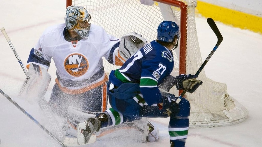 Vancouver Canucks defenseman Ben Hutton (27) fails to get a shot past New York Islanders goalie Thomas Greiss (1) during overtime in an NHL hockey game Thursday, March 9, 2017, in Vancouver, British Columbia. (Jonathan Hayward/The Canadian Press via AP)