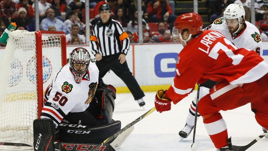 Chicago Blackhawks goalie Corey Crawford (50) stops a Detroit Red Wings center Dylan Larkin (71) shot in the second period of an NHL hockey game Friday, March 10, 2017, in Detroit. (AP Photo/Paul Sancya)