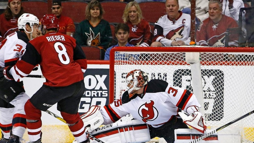 Arizona Coyotes right wing Tobias Rieder (8) scores a goal against New Jersey Devils goalie Cory Schneider, right, as Devils' Steven Santini, left, defends during the first period of an NHL hockey game Saturday, March 11, 2017, in Glendale, Ariz. (AP Photo/Ross D. Franklin)