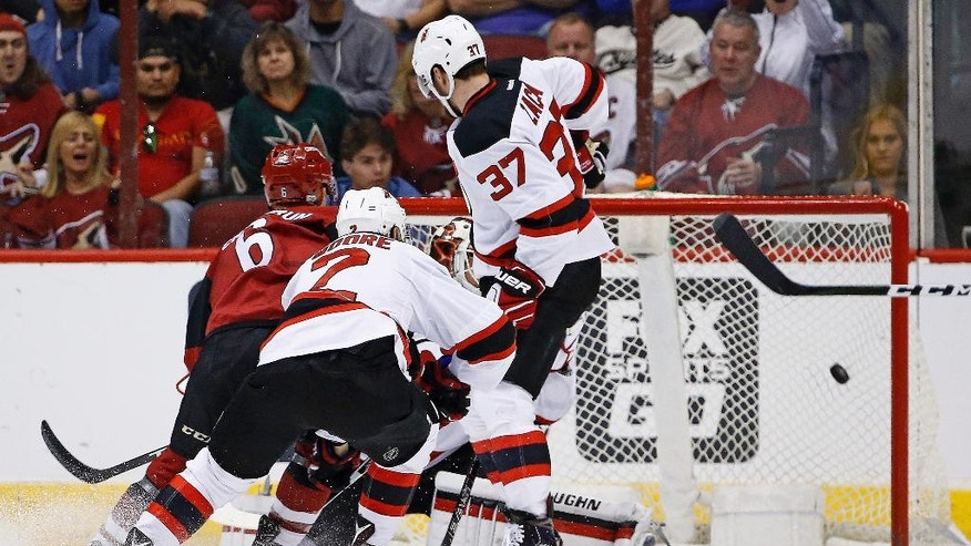 Arizona Coyotes defenseman Jakob Chychrun (6) gets the puck past New Jersey Devils center Pavel Zacha (37), John Moore (2) and goalie Cory Schneider, right, for a goal during the first period of an NHL hockey game Saturday, March 11, 2017, in Glendale, Ariz. (AP Photo/Ross D. Franklin)