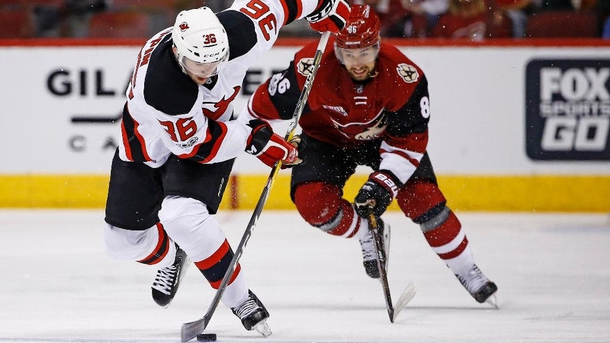 New Jersey Devils right wing Nick Lappin (36) skates with the puck in front of Arizona Coyotes right wing Josh Jooris (86) during the first period of an NHL hockey game Saturday, March 11, 2017, in Glendale, Ariz. (AP Photo/Ross D. Franklin)