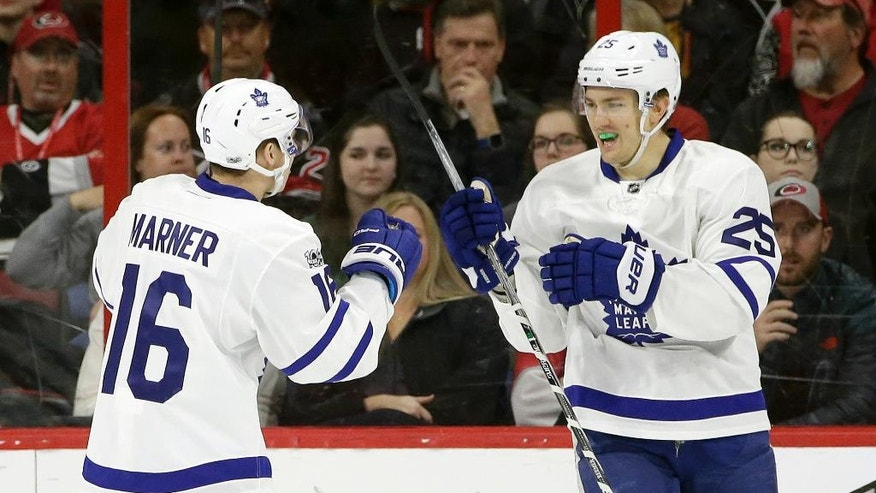 Toronto Maple Leafs' Mitchell Marner (16) congratulates James van Riemsdyk (25) following van Riemsdyk's goal against the Carolina Hurricanes during the second period of an NHL hockey game in Raleigh, N.C., Saturday, March 11, 2017. Toronto won 3-2 in overtime. (AP Photo/Gerry Broome)