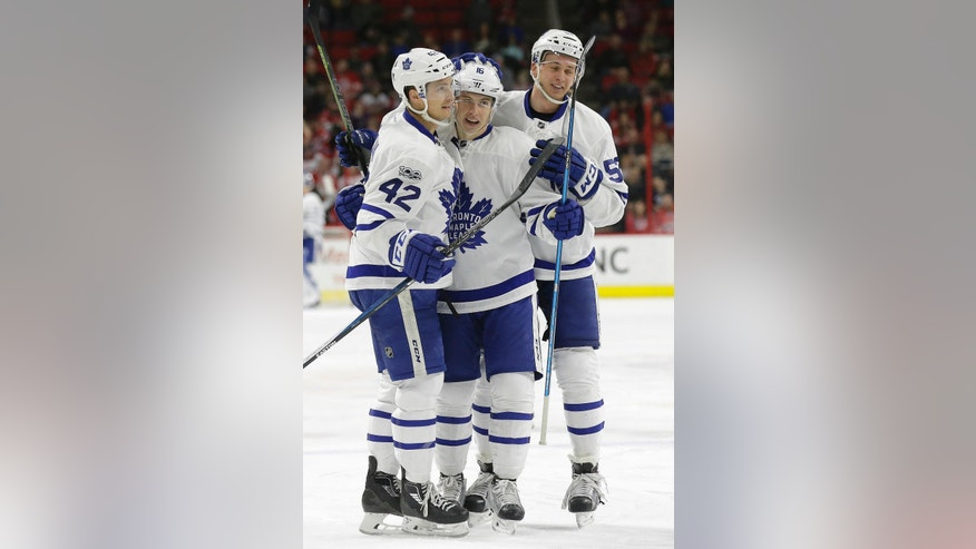 Toronto Maple Leafs' Tyler Bozak (42) and Martin Marincin, right, of Slovakia, congratulate Mitchell Marner (16) following Marner's goal against the Carolina Hurricanes during the first period of an NHL hockey game in Raleigh, N.C., Saturday, March 11, 2017. Toronto won 3-2 in overtime. (AP Photo/Gerry Broome)