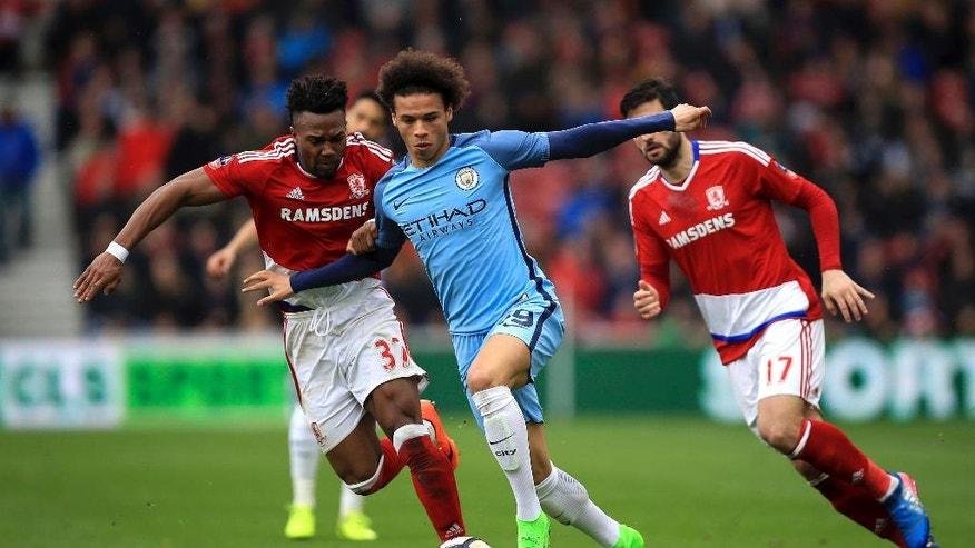Manchester City's Leroy Sane, centre, and Middlesbrough's Adama Traore, left, in action during their English FA Cup quarter final soccer match at the Riverside Stadium in Middlesbrough, England, Saturday March 11, 2017. (Mike Egerton/PA via AP)