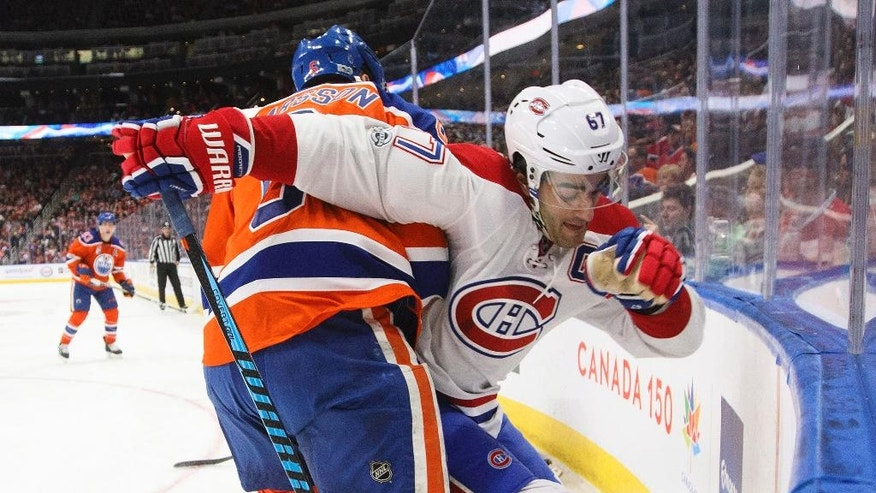 Montreal Canadiens left wing Max Pacioretty (67) and Edmonton Oilers defenseman Adam Larsson (6) battle for the puck during first-period NHL hockey game action in Edmonton, Alberta, Sunday, March 12, 2017. (Jason Franson/The Canadian Press via AP)