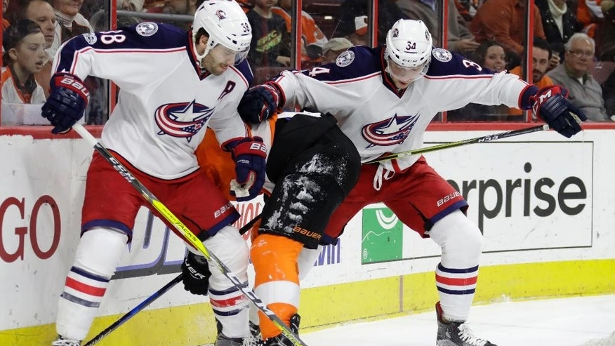 Columbus Blue Jackets' Boone Jenner, left, and Josh Anderson, right, battle against Philadelphia Flyers' Ivan Provorov for the puck during the first period of an NHL hockey game, Monday, March 13, 2017, in Philadelphia. (AP Photo/Matt Slocum)